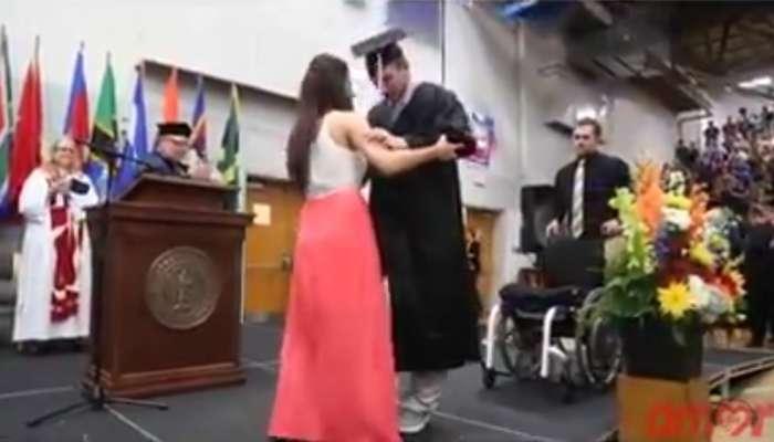 Discapacitado es ayudado por su novia para recibir el titulo en la ceremonia de graduacion